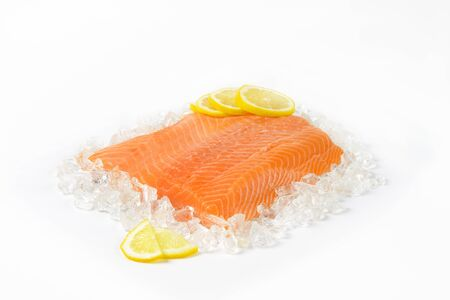 raw salmon fillet with slices of lemon on ice