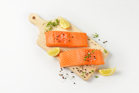 raw salmon fillets with salt, peppercorns, thyme and lemon