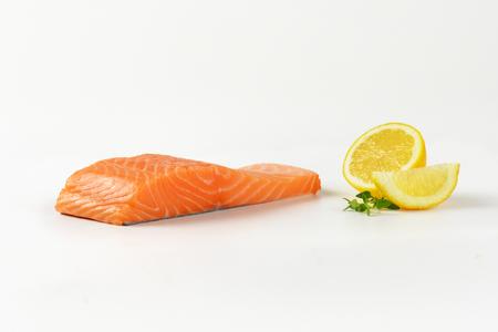 Fresh salmon fillet and lemon on white background Stock Photo