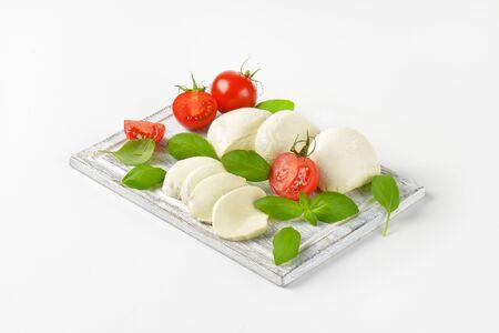 mozzarella, tomatoes and fresh basil leaves on cutting board