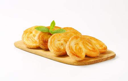 pasteleria francesa: Elephant ear cookies coated with sugar on a cutting board