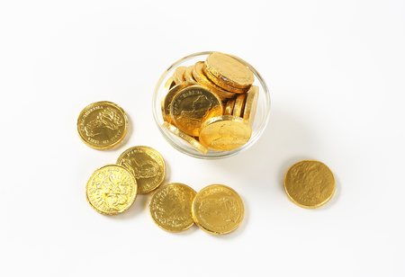 Gold foiled chocolate coins in glass bowl and next to it