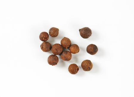 allspice: handful of allspice berries on white background