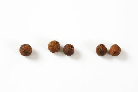 five berries of allspice on white background