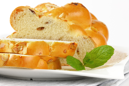 detail of sliced loaf of sweet braided bread with almonds and raisins Stock Photo