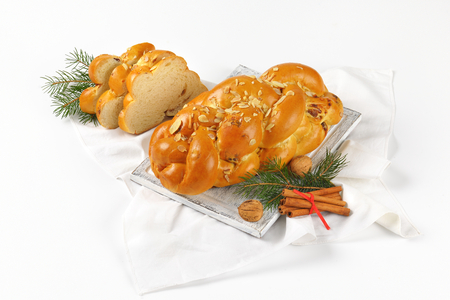 loaf of Christmas sweet braided bread on wooden cutting board and white napkin Stock Photo