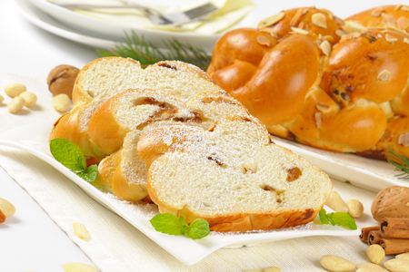 whole and sliced sweet braided bread with almonds and raisins