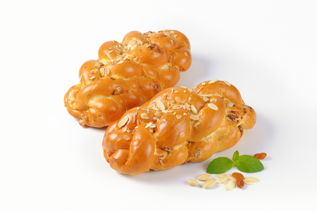 two loaves of sweet braided bread with almonds and raisins on white background