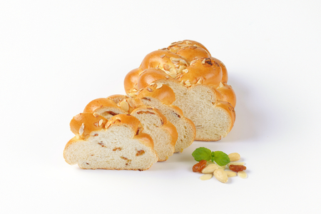 sliced loaf of Christmas sweet braided bread with almonds and raisins Stock Photo