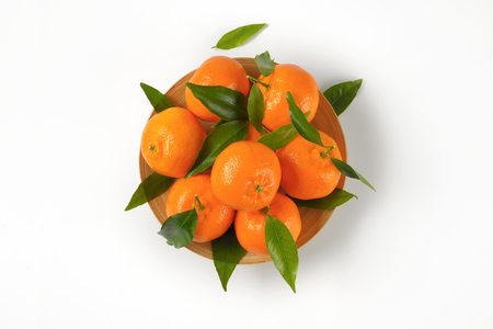 plate of ripe tangerines on white background