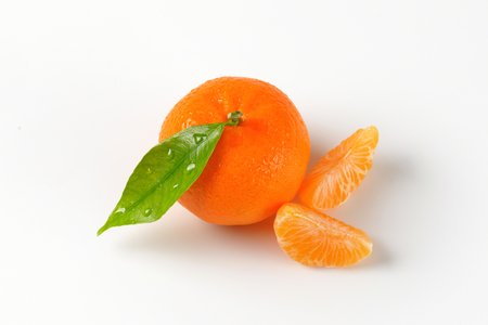 freshly washed tangerine with separated segments on white background