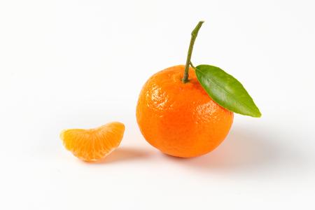 segmentar: tangerine with separated segment on white background Foto de archivo