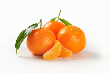 three whole tangerines with separated segments on white background