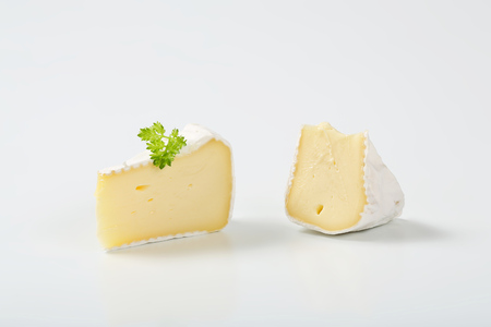 rinds: two slices of white rind cheese with parsley on white background