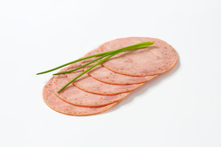 slices of deli meat with chives on white background Stock Photo