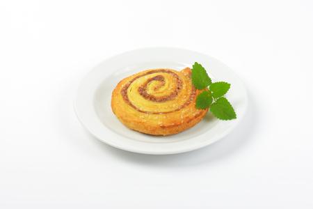 sweet cinnamon roll on white plate