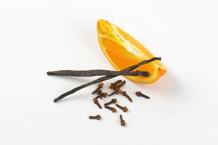 slice of orange, vanilla pods and cloves on white background