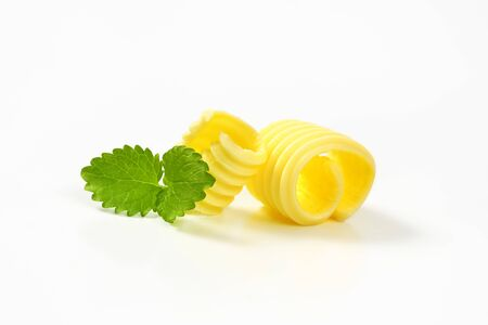 Curls of fresh butter on white background