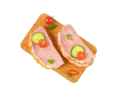 two faced: two open faced ham sandwiches on wooden cutting board