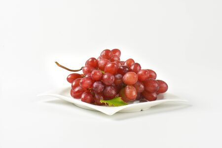 white washed: bunch of washed red grapes on white plate