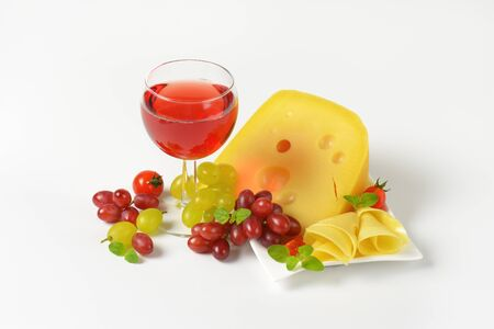 yellow medium-hard cheese with eyes, glass of red wine and fresh grapes Stock Photo