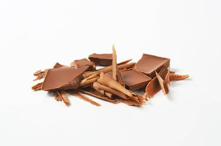 chocolate shavings: Milk chocolate shavings and pieces on white background Stock Photo