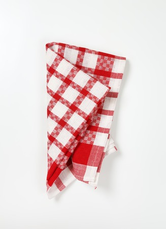 red and white checkered dish towel on white background