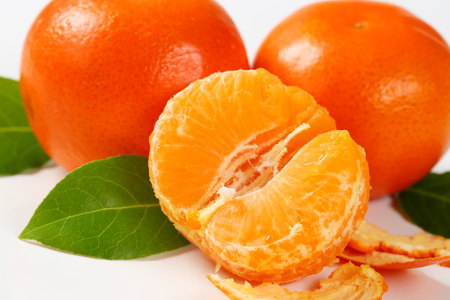 clementines: detail of fresh seedless tangerines - peeled and unpeeled Stock Photo