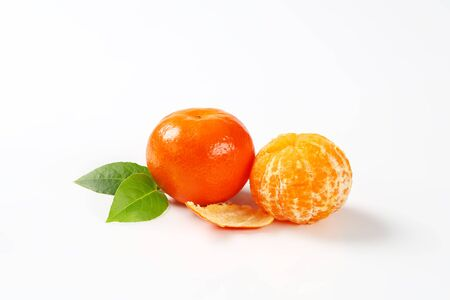 clementines: two fresh peeled and unpeeled clementines on white background