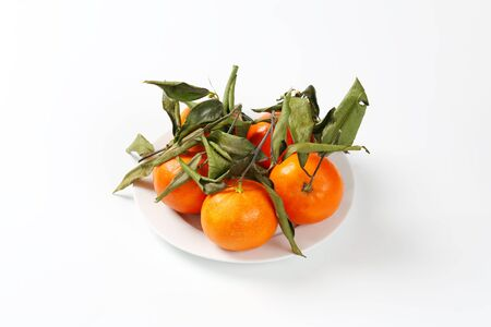 clementines: plate of fresh tangerines with leaves on white background Stock Photo