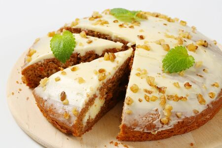 Carrot cake with cream cheese icing topped with chopped walnuts