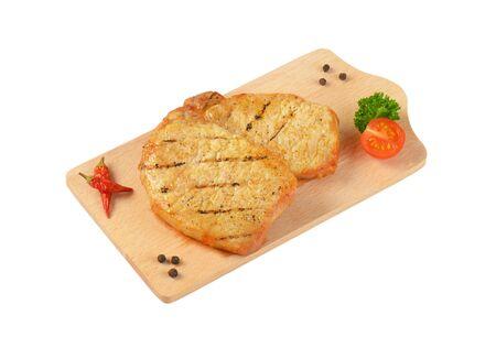 pork chops: Two grilled honey glazed pork chops on cutting board Stock Photo
