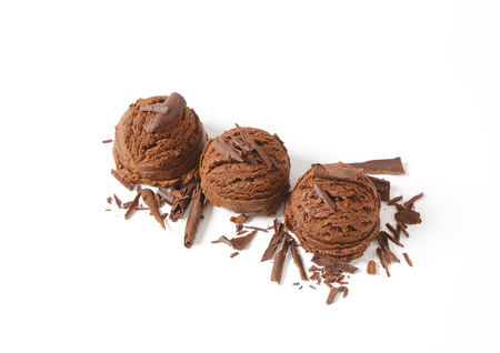 chocolate shavings: three scoops of chocolate ice cream with chocolate shavings on white plate