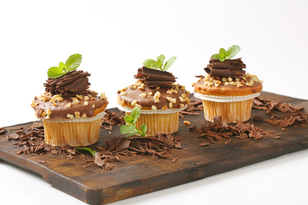Muffins with chocolate topping and chopped nuts Stock Photo
