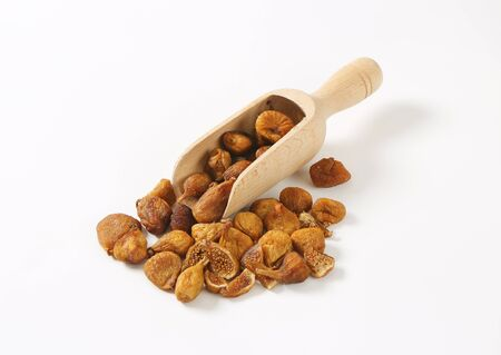 wooden scoop: dried figs in wooden scoop and next to it Stock Photo