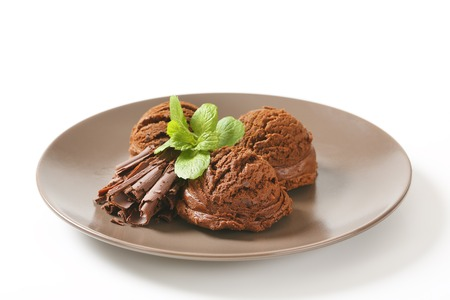 chocolate shavings: three scoops of chocolate ice cream with mint and chocolate shavings on brown plate Stock Photo