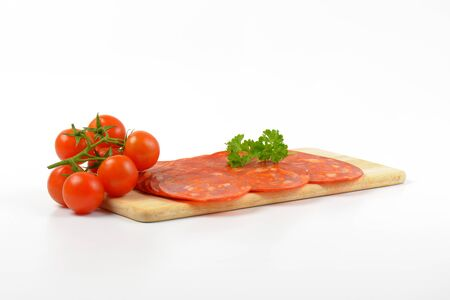 slices of chorizo salami and cherry tomatoes on wooden cutting board