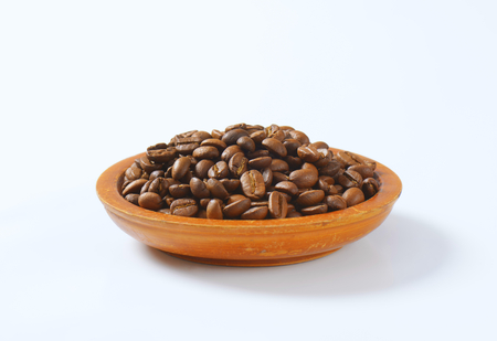 fairtrade: bowl of roasted coffee beans on white background