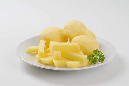 raw whole and chipped potatoes on plate Stock Photo