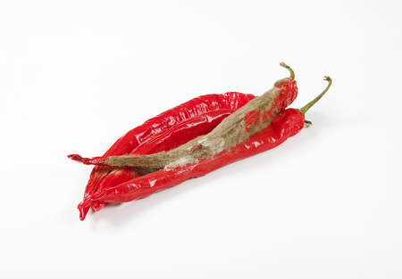 shrinking and mouldy chili peppers on white background Stock Photo