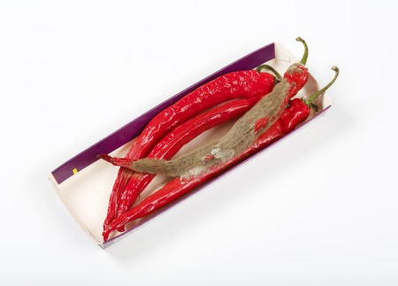 chili peppers: shrinking and mouldy chili peppers in paper box Stock Photo