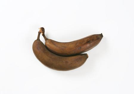overripe: two brown overripe bananas on white background