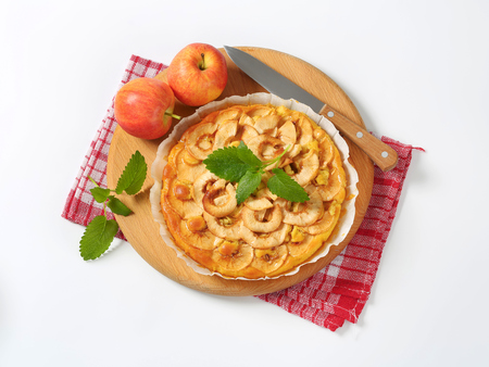 apple tart and fresh apples on round wooden cutting board