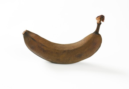 uneatable: brown overripe banana on white background Stock Photo