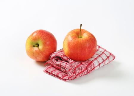two ripe apples on checkered dishtowel Stock Photo