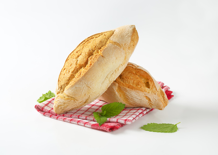 diamond shaped: two diamond shaped rustic bread rolls on checkered dishtowel