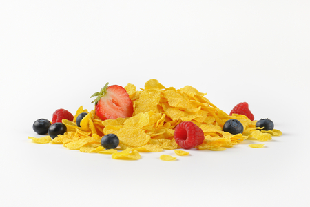 pile of corn flakes with berry fruits on white background