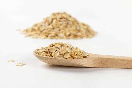 spoon of oat flakes on white background - close up