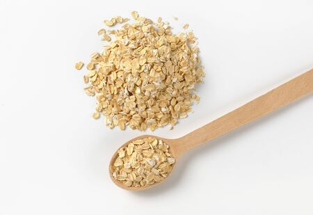 pile of oat flakes and wooden spoon on white background