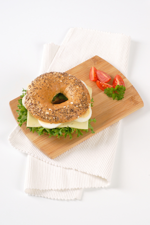 bagel sandwich with eggs and cheese on wooden cutting board Stock Photo